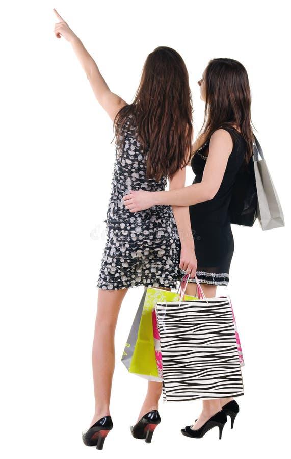 后面观点的二有购物袋的妇女 免版税库存照片