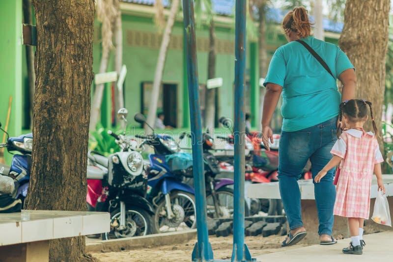 后面观点的亚裔母亲带领她的女儿学校 免版税库存照片
