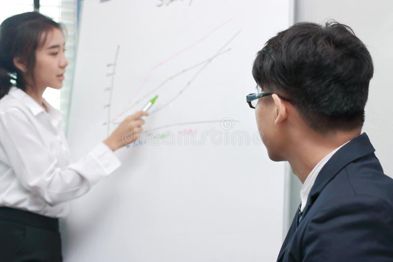 后面观点的亚裔经理从他的在会议之间的同事被谈论在办公室 库存照片