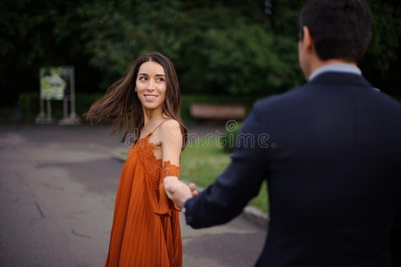 后面观点的人是握美好的妇女手的衣服 库存照片
