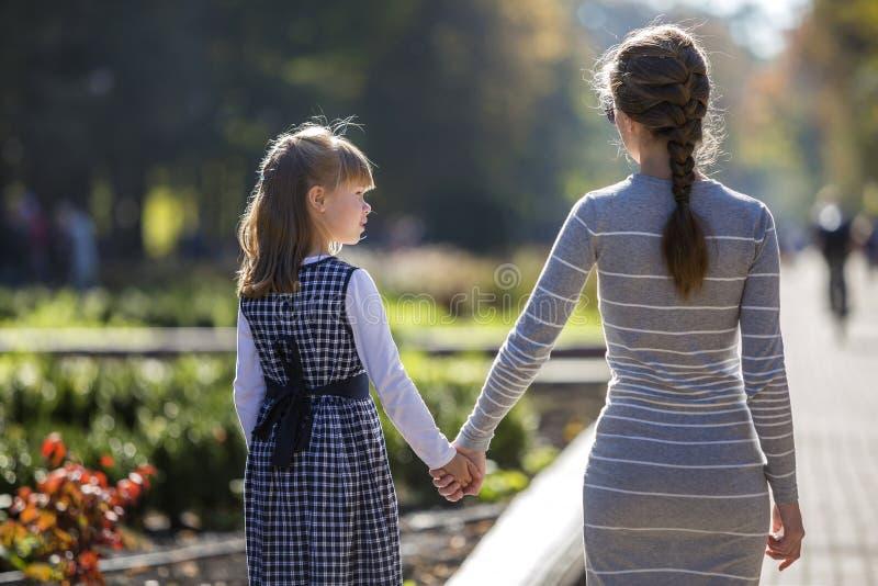 后面观点的儿童女孩和母亲结合在一起使手在温暖的天户外的礼服的晴朗的背景的 图库摄影