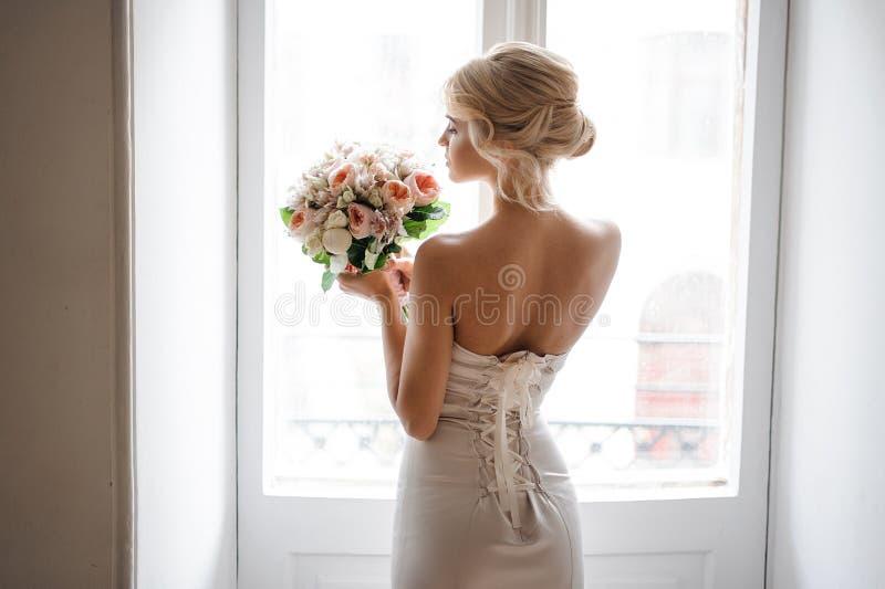 后面观点的典雅的白肤金发的新娘在拿着婚礼花束的一件白色礼服穿戴了 免版税库存图片