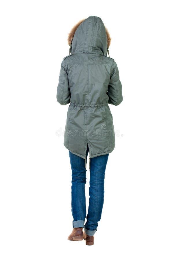 后面观点的冬天夹克的走的妇女有敞篷的 免版税库存照片