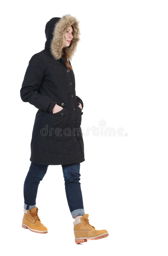 后面观点的冬天夹克的走的妇女有敞篷的 Beautifu 免版税库存照片