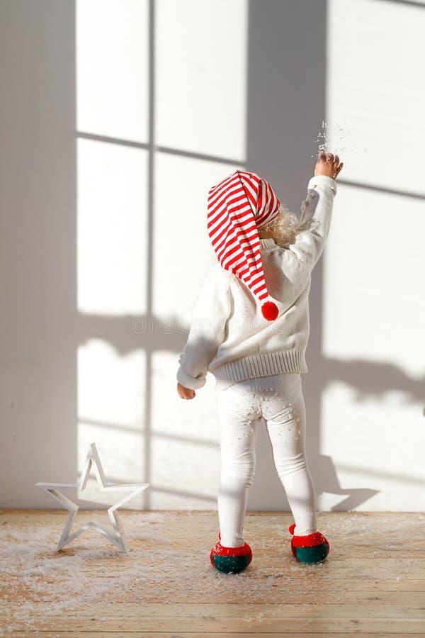 后面观点的可爱的小孩子矮子穿白色服装、圣诞老人s帽子和矮子s鞋子,与人为雪的戏剧,立场 免版税库存照片