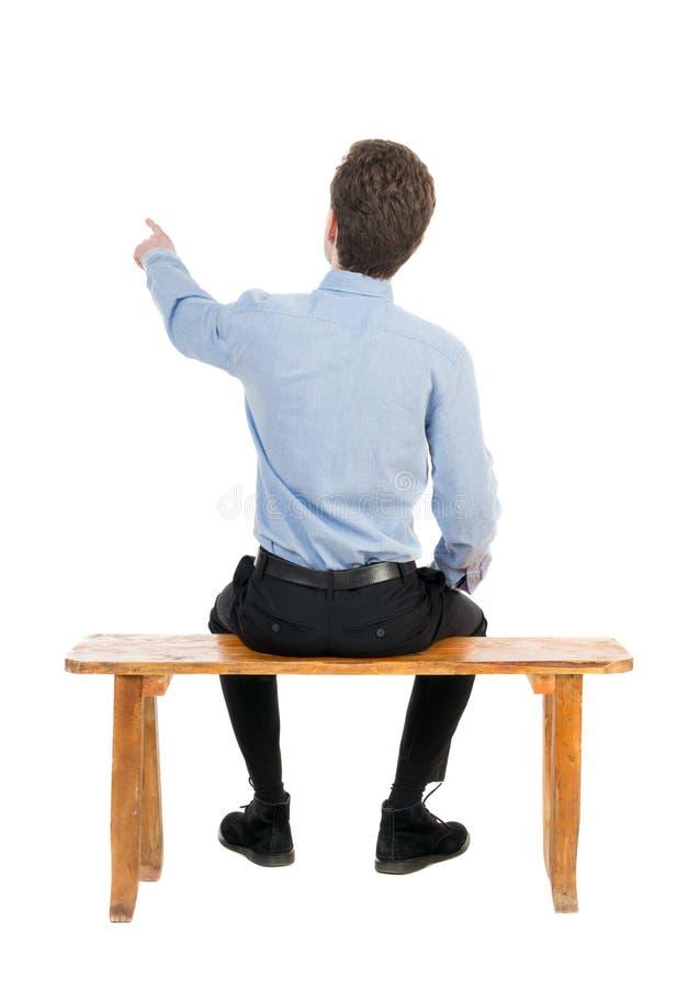 后面观点的商人坐椅子和指向 库存图片