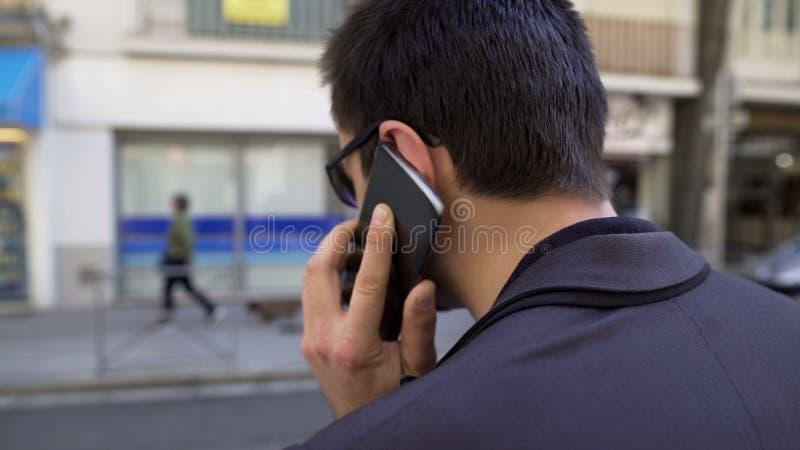 后面观点的商人讨论问题由电话城市街道,繁忙的生活方式 免版税库存照片
