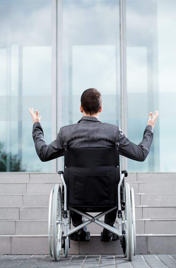 后面观点的在台阶前面的一个残疾人 库存照片