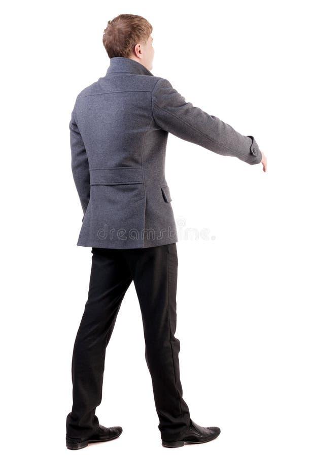 后面观点的在外套的商人提供援助握手 图库摄影