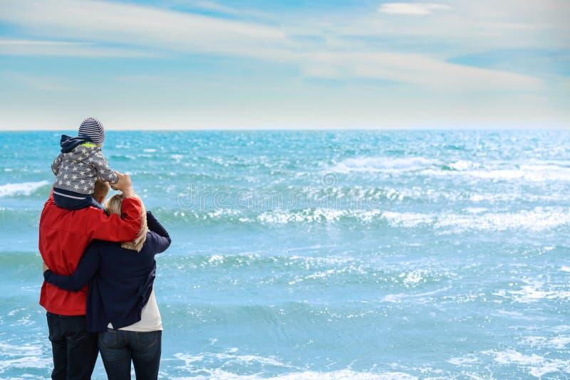 后面观点的在热带海滩的一个愉快的家庭暑假 免版税库存图片