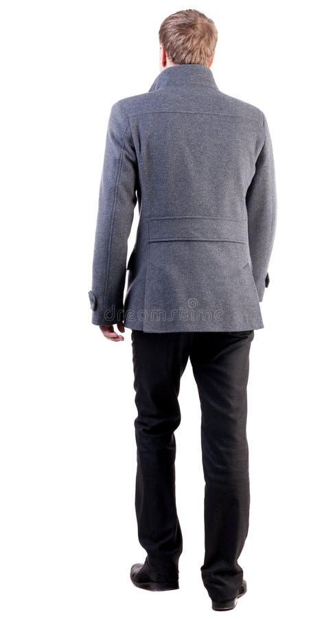 后面观点的外套的去的英俊的商人 库存照片