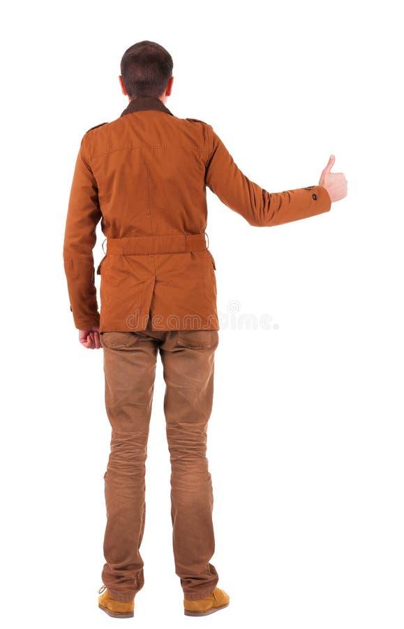 后面观点的夹克的人显示赞许 库存照片