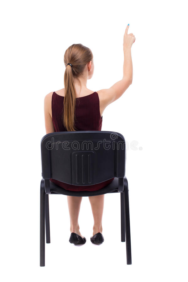后面观点的妇女坐椅子和指向 免版税库存图片