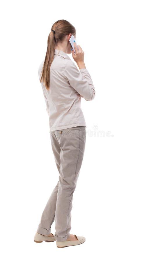 后面观点的妇女谈话在电话 免版税图库摄影