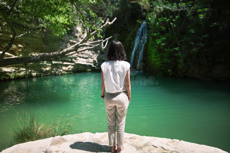 后面观点的少妇享用在美丽的湖的瀑布 免版税库存图片
