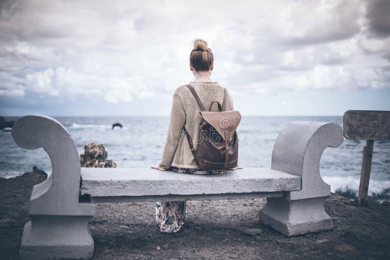 后面观点的少妇长的礼服的和有背包的坐石长凳由海 库存照片