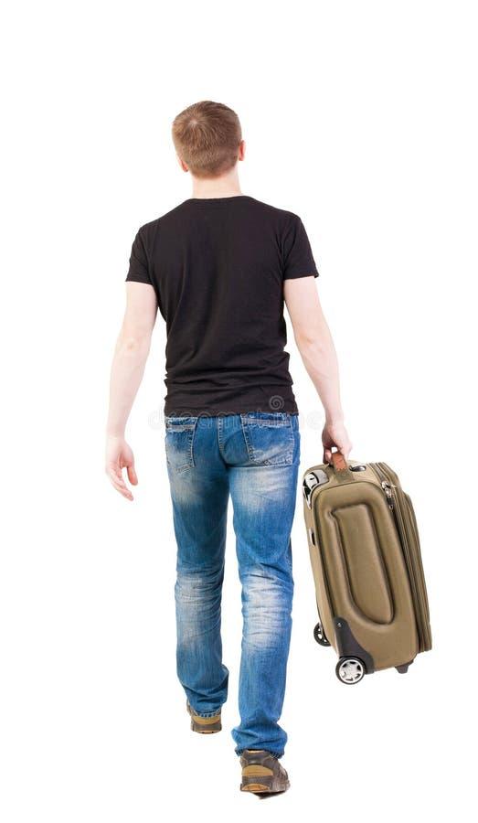 后面观点的带着手提箱的走的人 库存照片