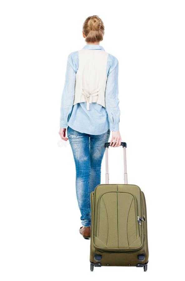 后面观点的带着手提箱的走的妇女 图库摄影
