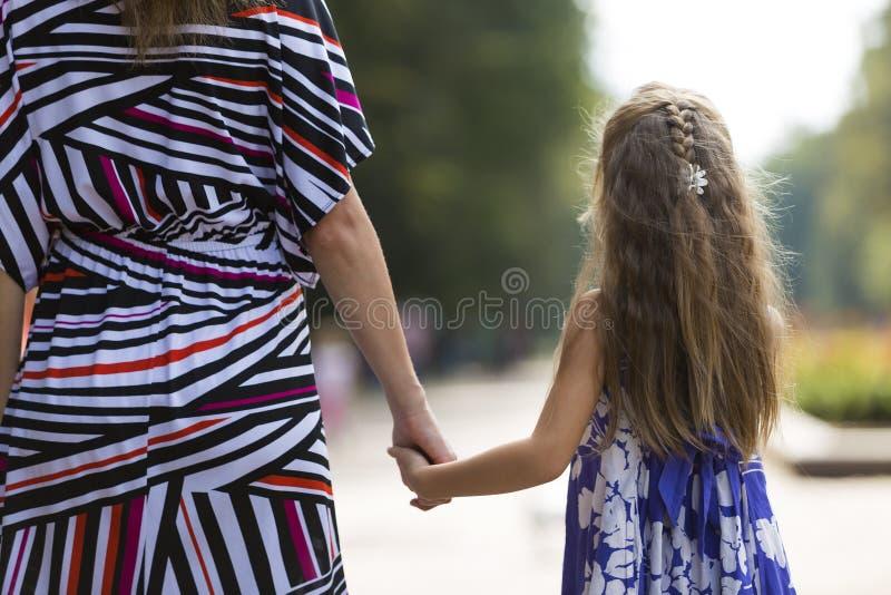 后面观点的年轻白肤金发的长发可爱的妇女和小 免版税库存图片
