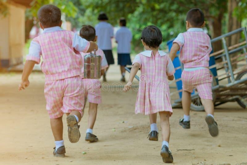 后面观点的幼儿园学生跑回到教室 库存图片