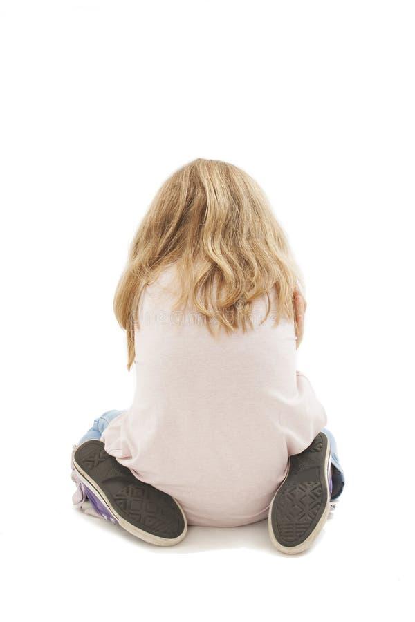 后面观点的恼怒的女孩用被折叠的手,坐膝盖 免版税库存图片