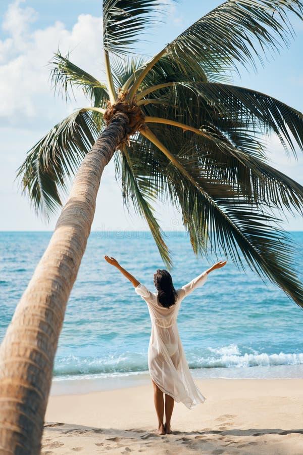 后面观点的愉快的年轻女人享受她的热带海滩假期身分在棕榈树下 免版税库存图片