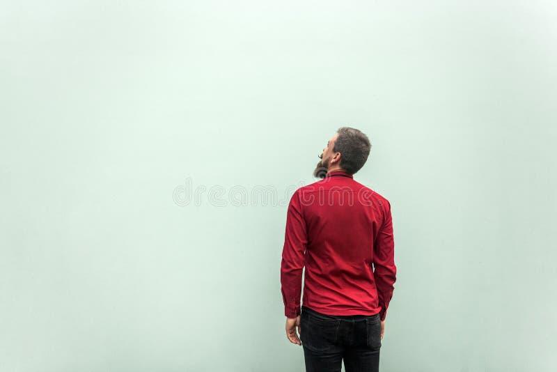 后面观点的成功商人,在灰色背景 查寻和作梦 图库摄影