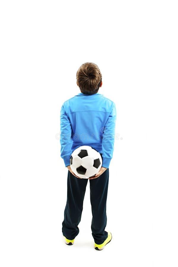 后面观点的拿着足球的运动服的一个孩子 库存照片