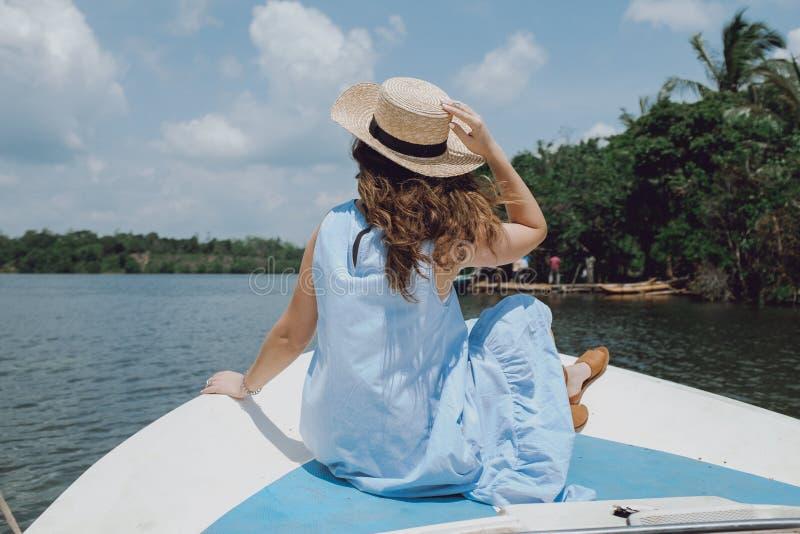 后面观点的放松在小船和看河的草帽的一个少妇 免版税库存图片