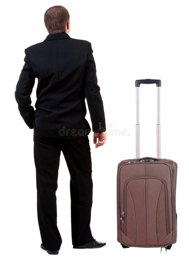 后面观点的旅行与suitcas的黑衣服的商人 免版税库存图片