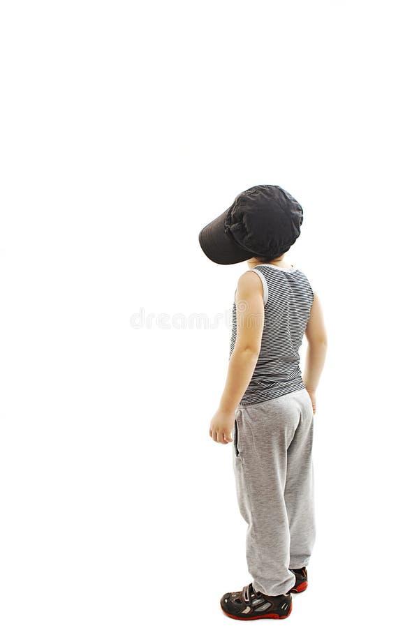 后面观点的时兴的小男孩 看墙壁的节律唱诵的音乐样式 免版税库存图片
