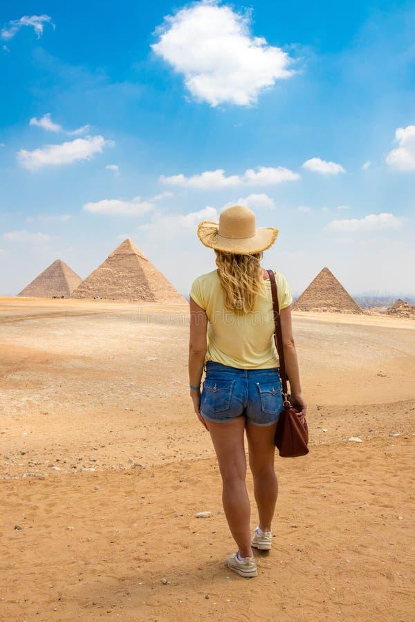 后面观点的有美丽的金发的年轻女性 观看吉萨棉的伟大的金字塔一名单身妇女的后面看法画象 库存照片