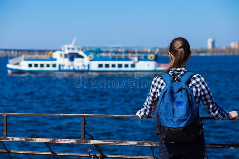 后面观点的有背包身分的旅游妇女在海附近的码头在晴朗的春日 免版税库存图片