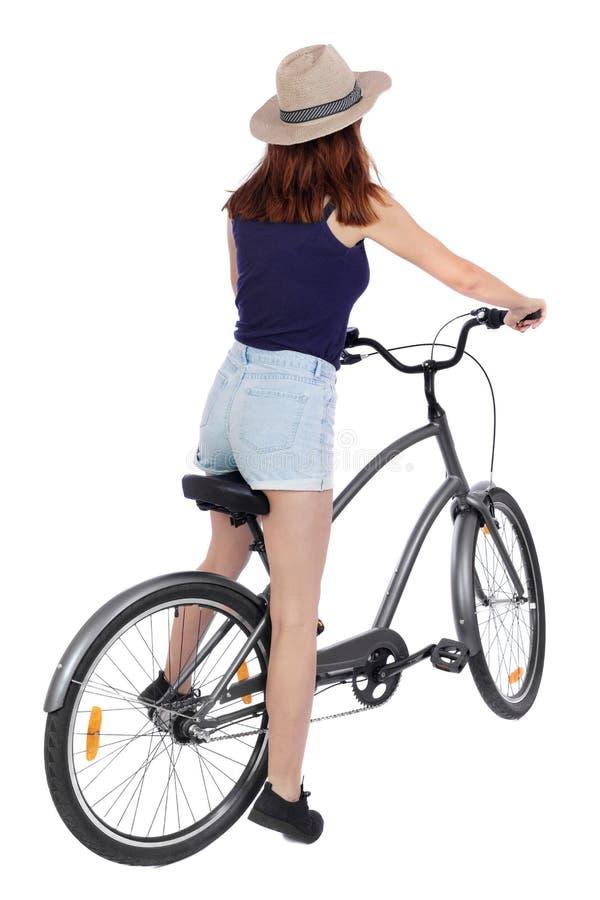 后面观点的有自行车的一名妇女 骑自行车者坐自行车 背面图人汇集 免版税库存照片