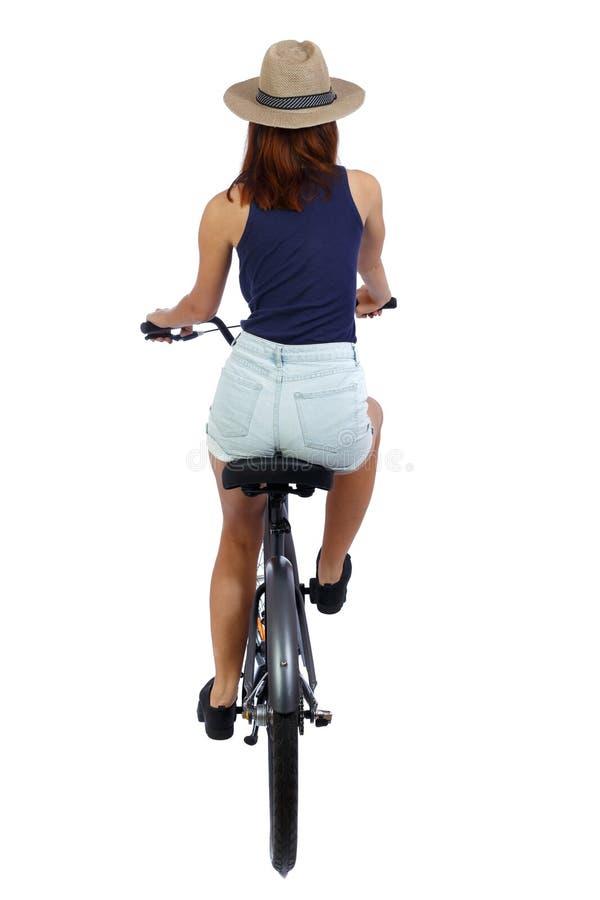 后面观点的有自行车的一名妇女 免版税库存图片