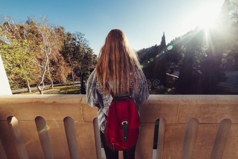 后面观点的有长的头发旅行的佩带的偶然牛仔裤的站立户外在日落时间的成套装备和背包美丽的妇女 库存图片
