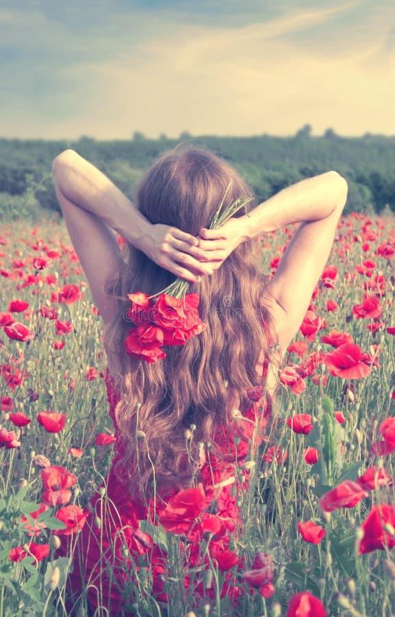 后面观点的有长的金发的一个少妇在拿着花的花束在鸦片领域的一件红色礼服 图库摄影