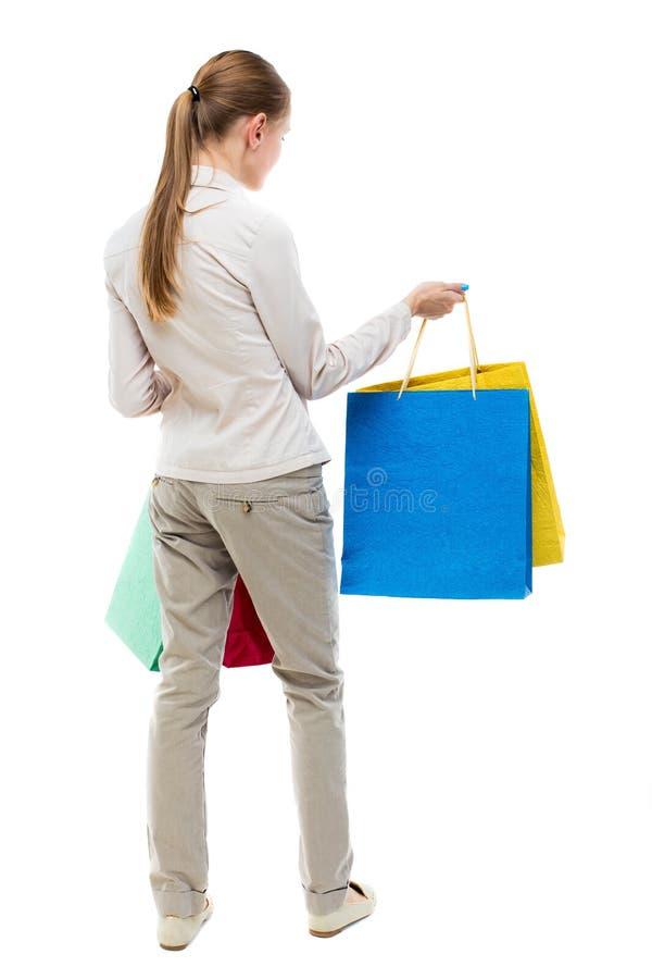 后面观点的有购物袋的妇女 免版税库存照片
