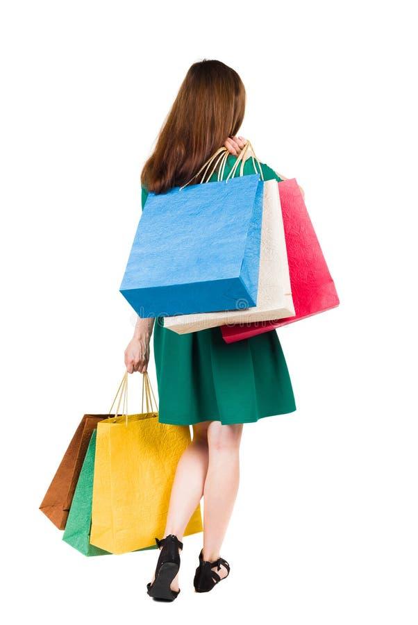后面观点的有购物袋的去的妇女妇女 免版税库存图片