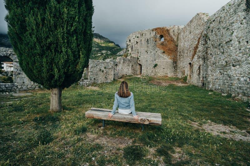后面观点的松弛妇女坐长凳在高大的树木附近 图库摄影