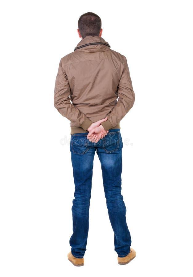 后面观点的查寻棕色的防风衣的英俊的人 免版税库存照片