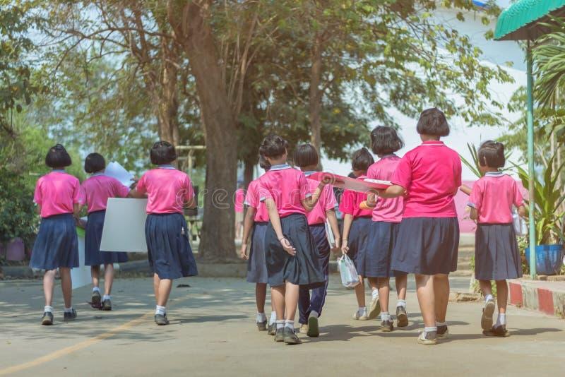 后面观点的桃红色衬衣和蓝色裙子步行的幸福主要女生对教室 免版税库存照片