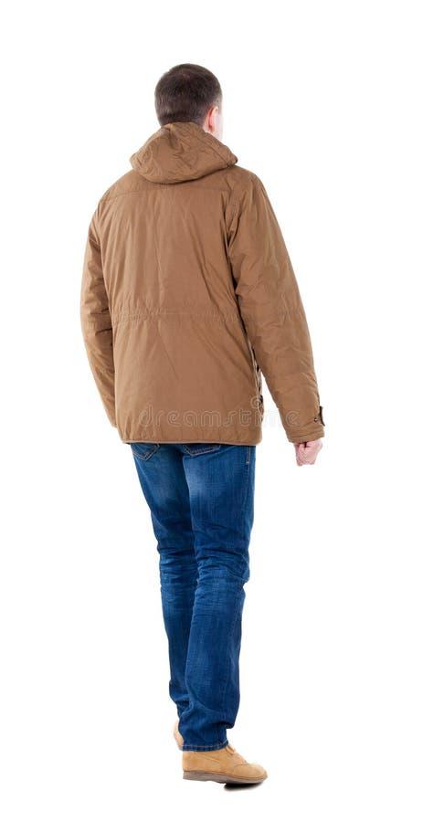 后面观点的棕色附头巾皮外衣的去的英俊的人 库存图片