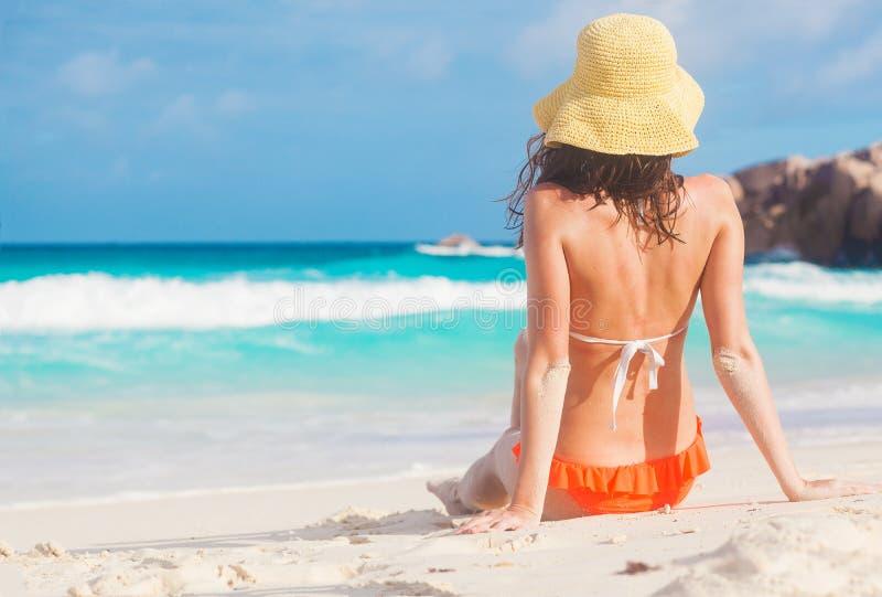 后面观点的比基尼泳装的长发妇女在热带海滩 免版税库存照片