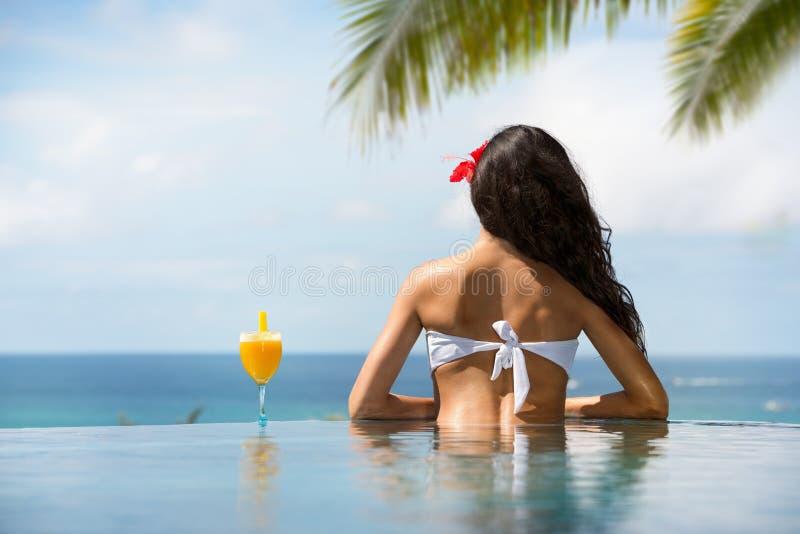 后面观点的比基尼泳装饮用的鸡尾酒的少妇 免版税库存照片