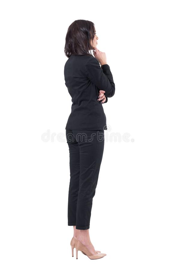 后面观点的注视着某事观看的衣服的典雅的女商人感兴趣 库存照片