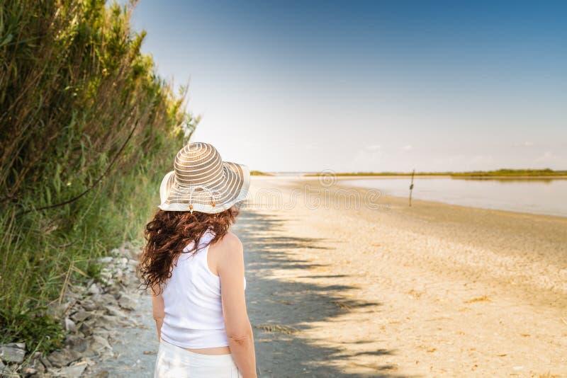 后面观点的海滩的妇女 库存图片