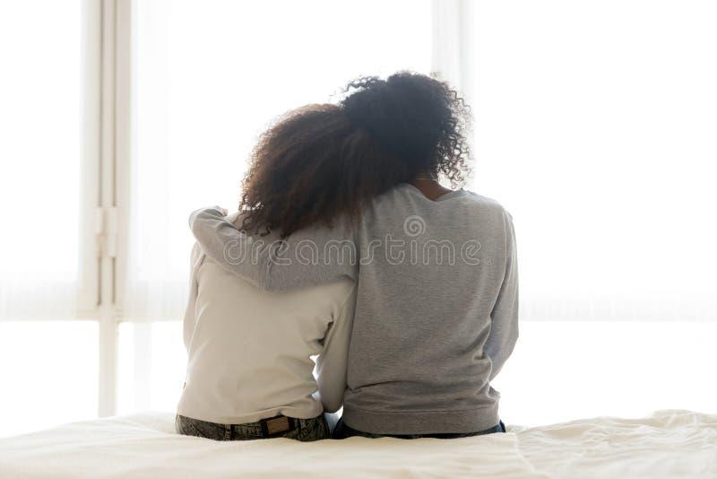后面观点的爱的妈妈拥抱青少年的女儿 免版税图库摄影
