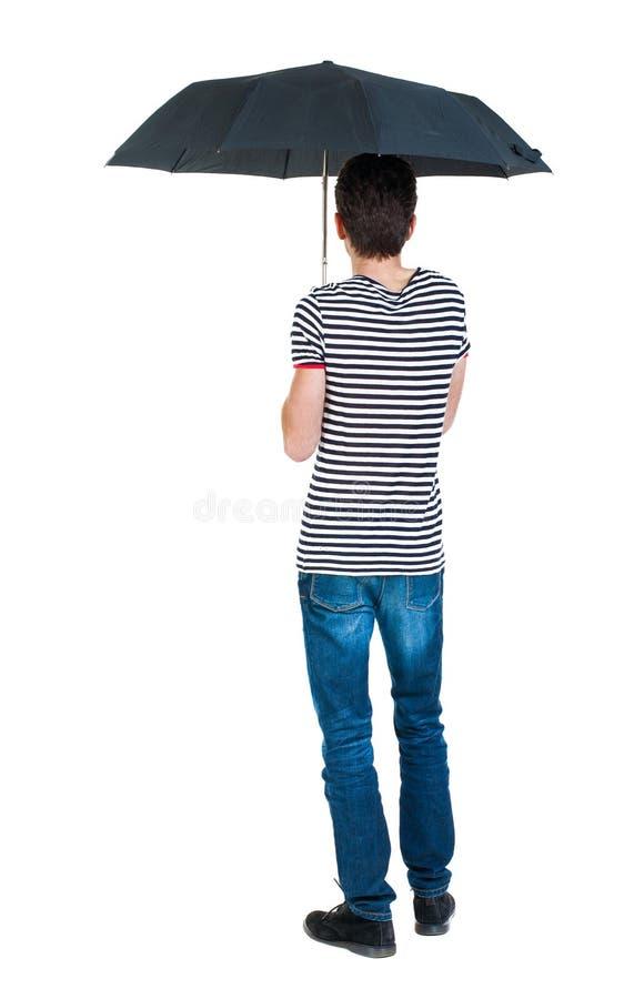 后面观点的牛仔裤的人在伞下 图库摄影