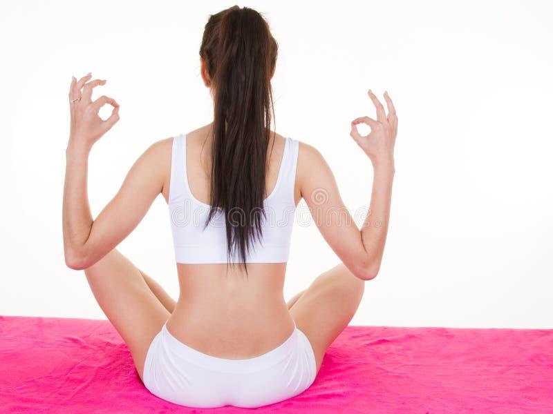 后面观点的瑜伽姿势的长发亭亭玉立的少妇 免版税库存图片